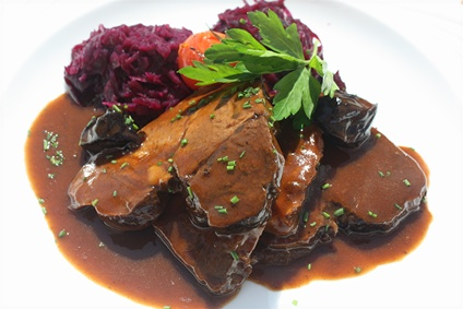 Teller mit Wildschweinbraten und Rotkohl aus der saisonalen Speisekarte